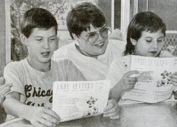 صورة ليندا مع طفلين يحملان نماذج من رسائل الحب